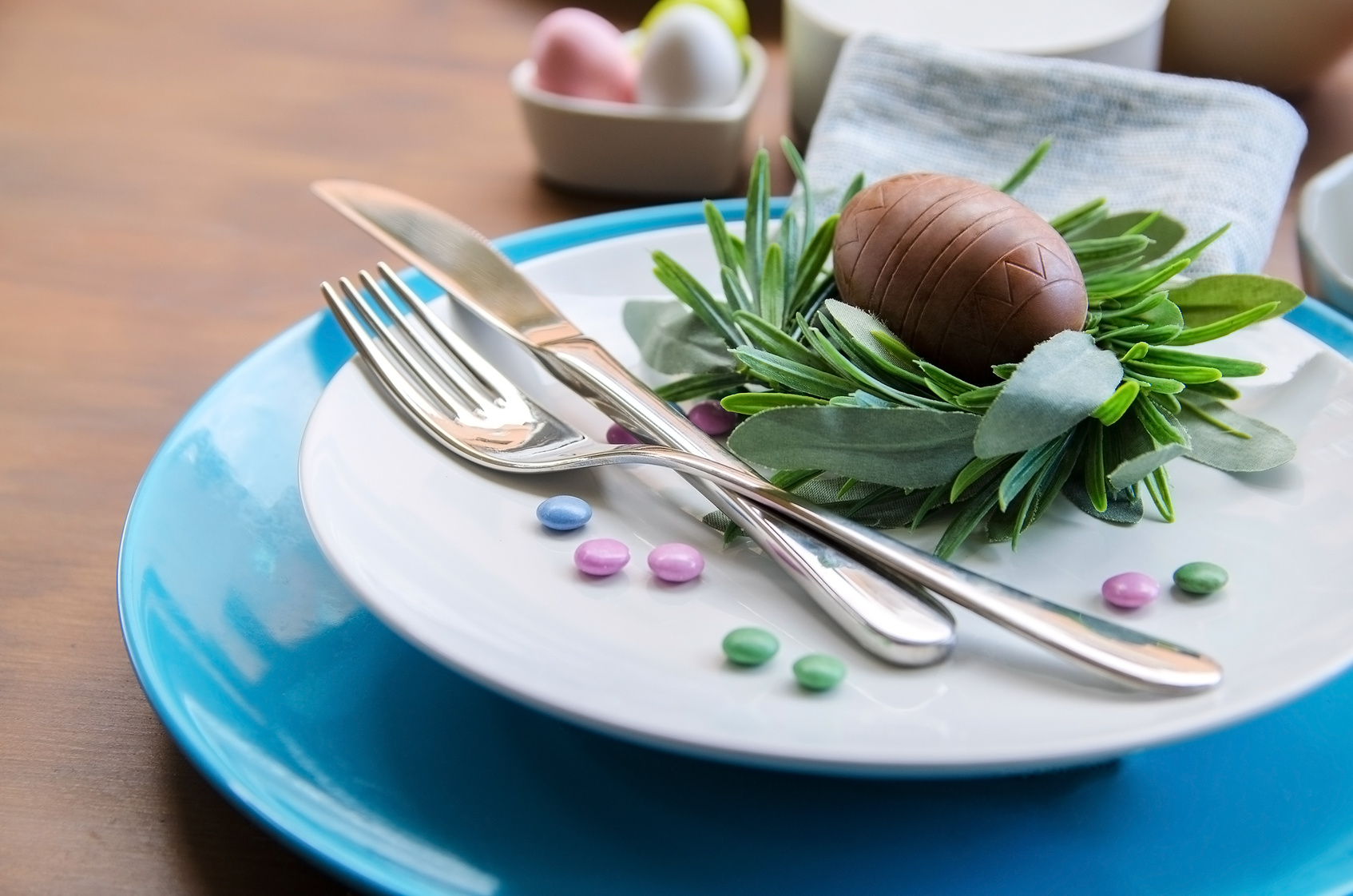 Beautiful Easter table settings, white and blue plate, silver cutlery, decorative nest with chocolate egg and colorful candy  on wooden background. Happy Easter concept.