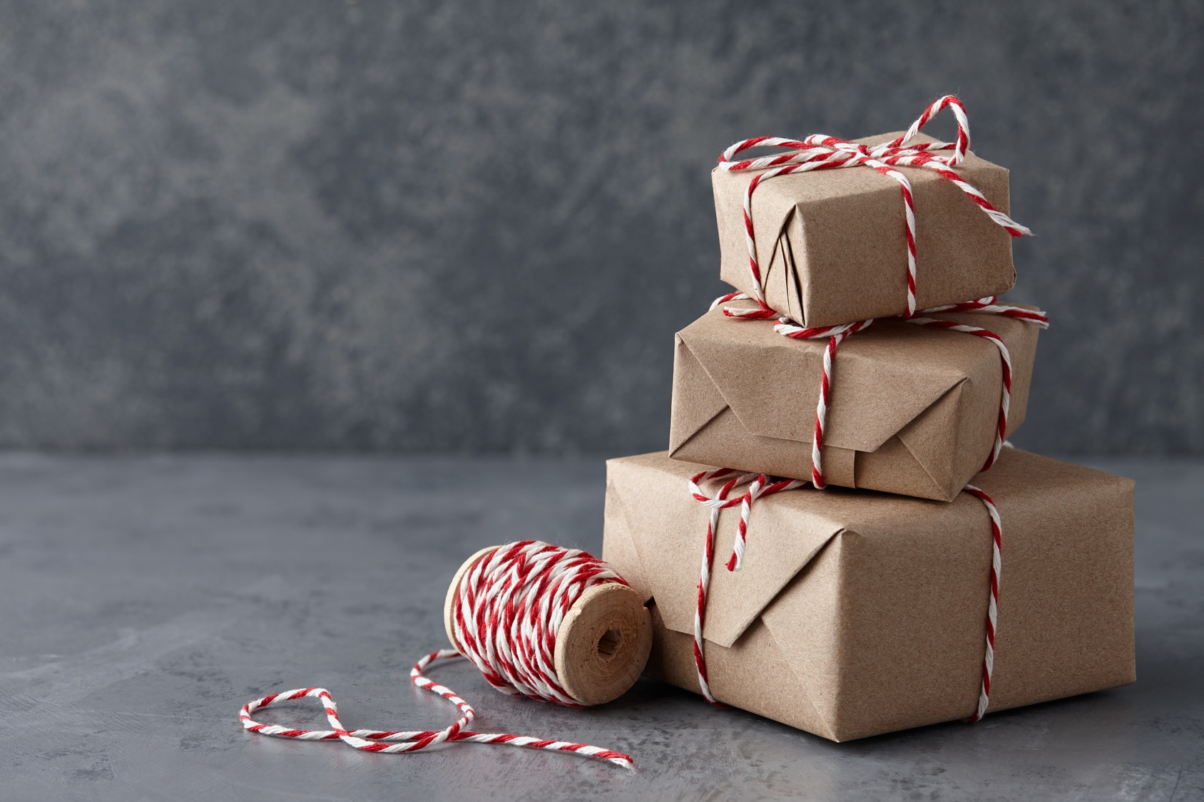 Christmas gift or present boxes wrapped in kraft paper with striped baker's twine string on textured stone background, copy space