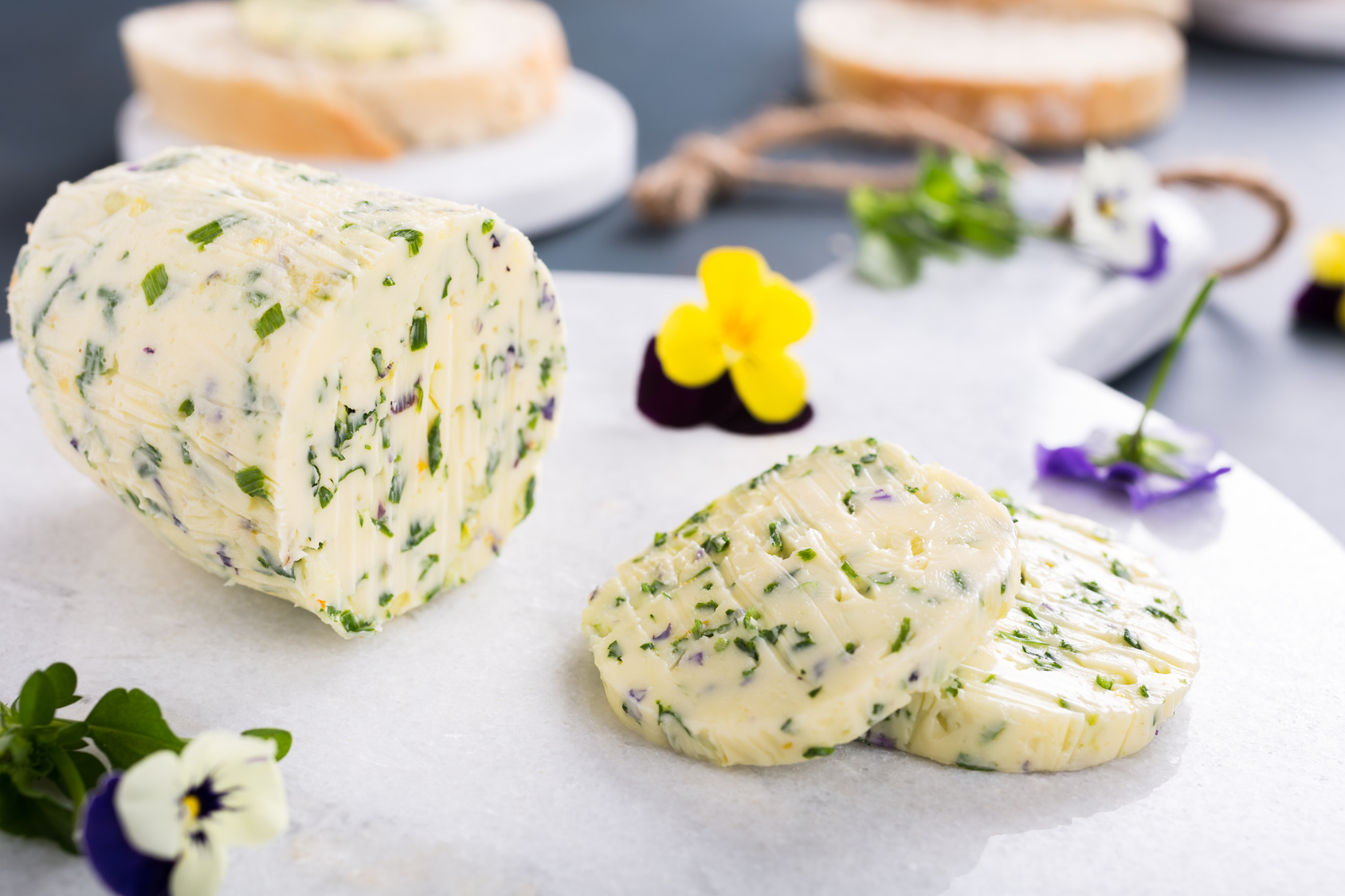 Herb butter with edible flowers on marble cutting board, healthy food.