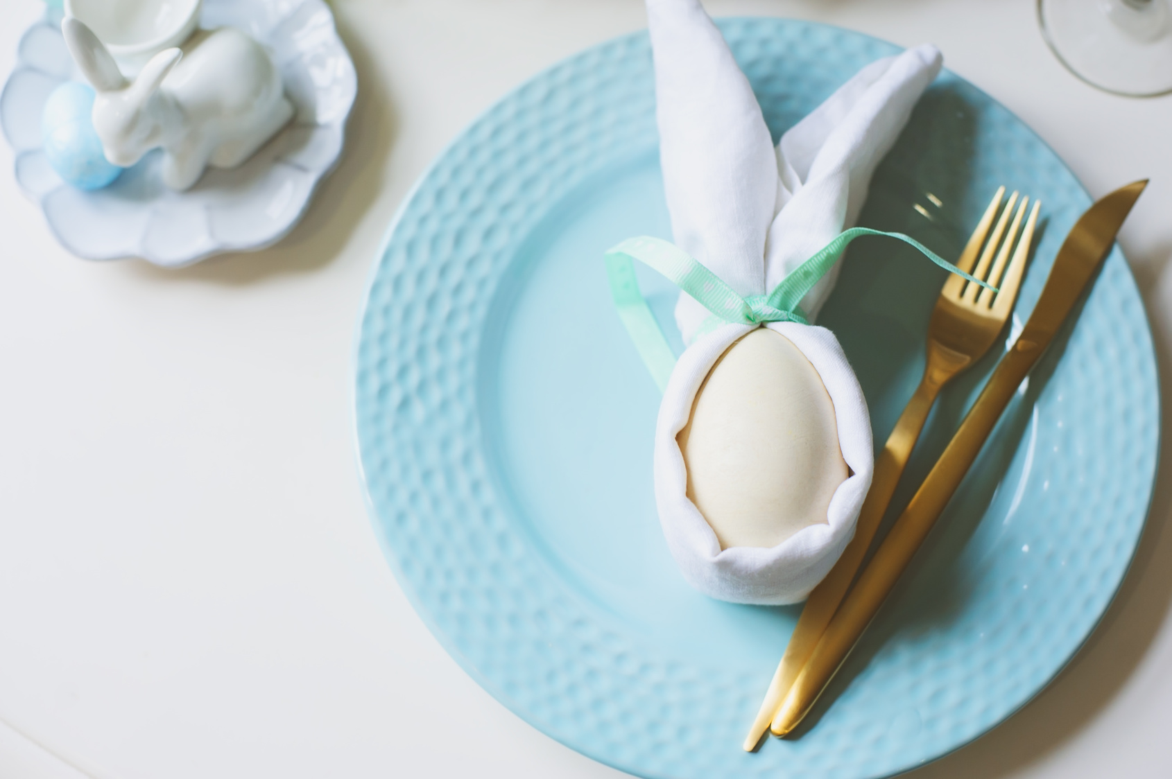 easter festive table. Guest dining place decorated with bunny napkin and egg, golden metalic cutlery and blue plate