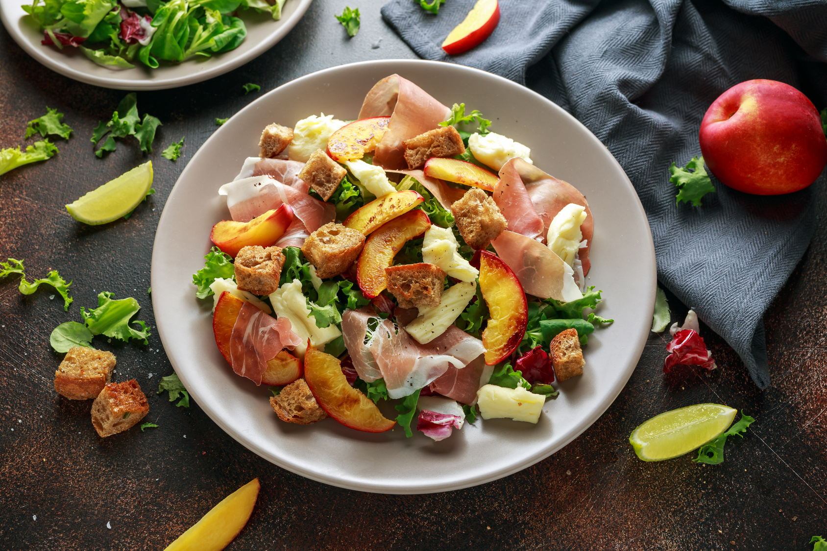 Fresh grilled peach salad with green mix, cheese, prosciutto and crouton.